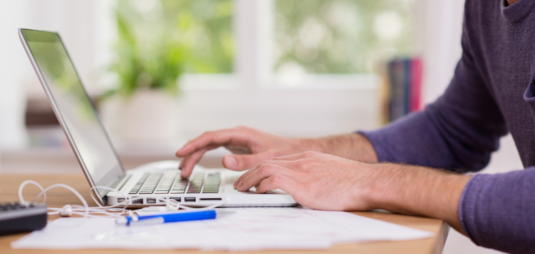 man writing his comments to a laptop