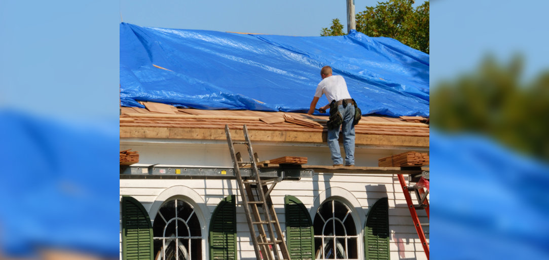 Man standing on a ladder repairing roof, with blue tarp, of church