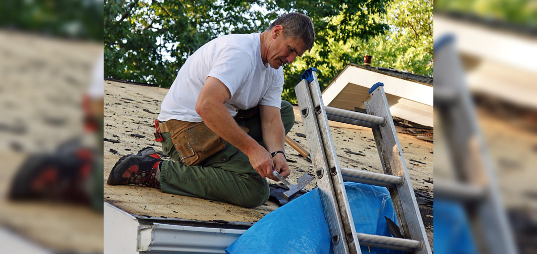 Man stripping shingles from a garage roof